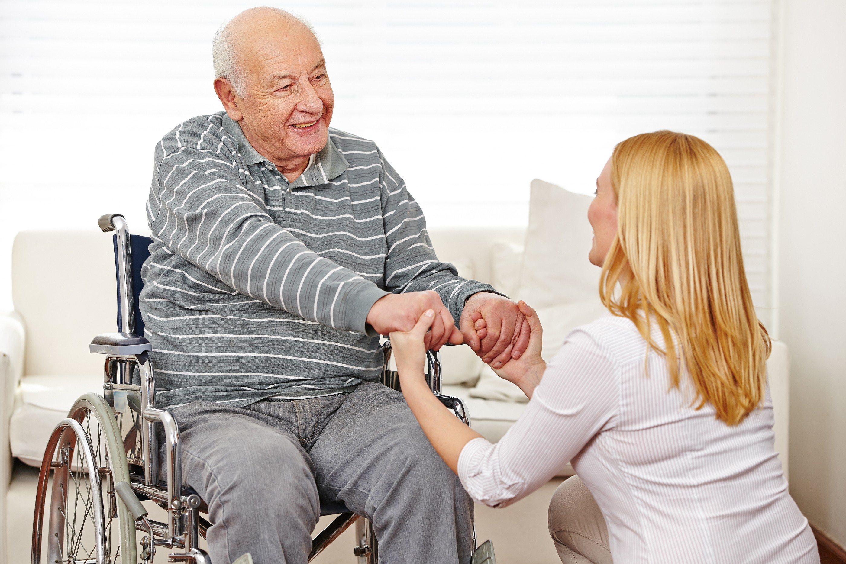 Woman holding hands of old man in wheelchair in a nursing home