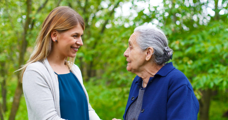 Senior woman with dementia outside with caregiver